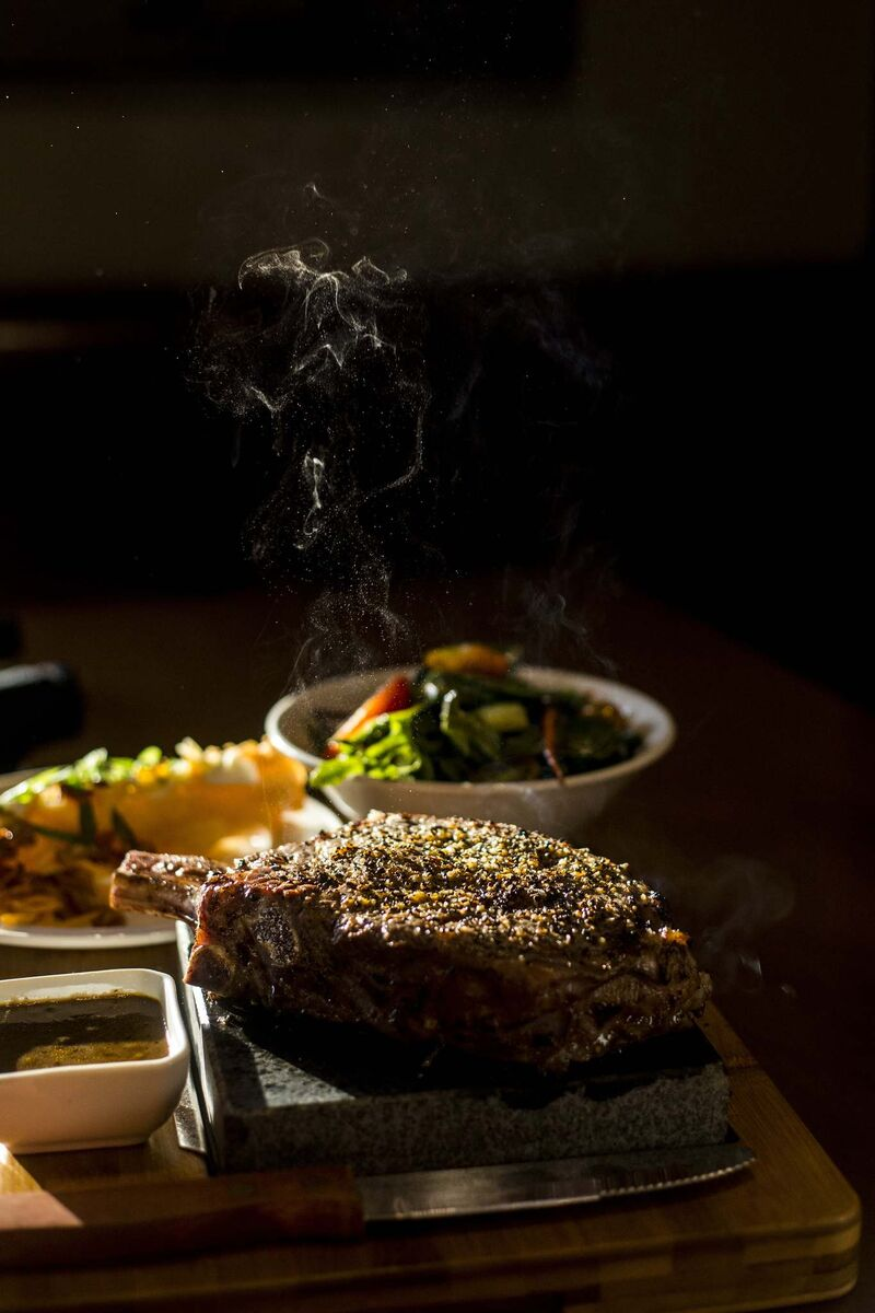 MIKAELA MACKENZIE / WINNIPEG FREE PRESS</p><p>A bone-in ribeye steak sizzles on a lava rock alongside a house salad and deep-fried mashed potatoes at Lot 88.</p>