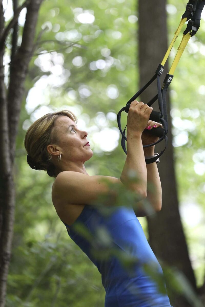 Julie McPetrie, a fitness consultant at Winnipeg's Reh-Fit Centre, hooks a TRX suspension trainer to a tree for an outdoor workout.</p></p>