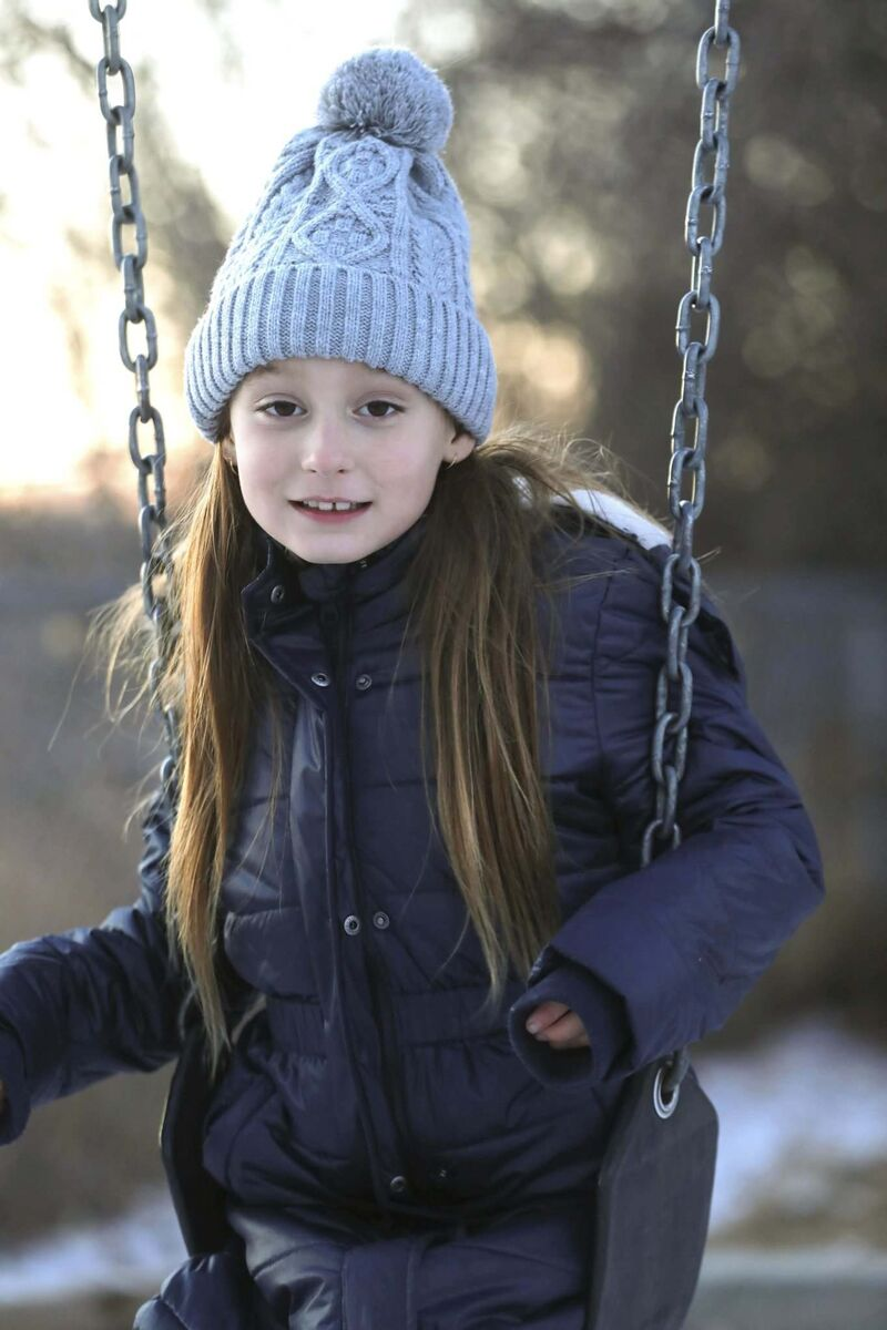 Emby Blum-Payne plays on a swing while out for a walk with her mom and dad.</p>
