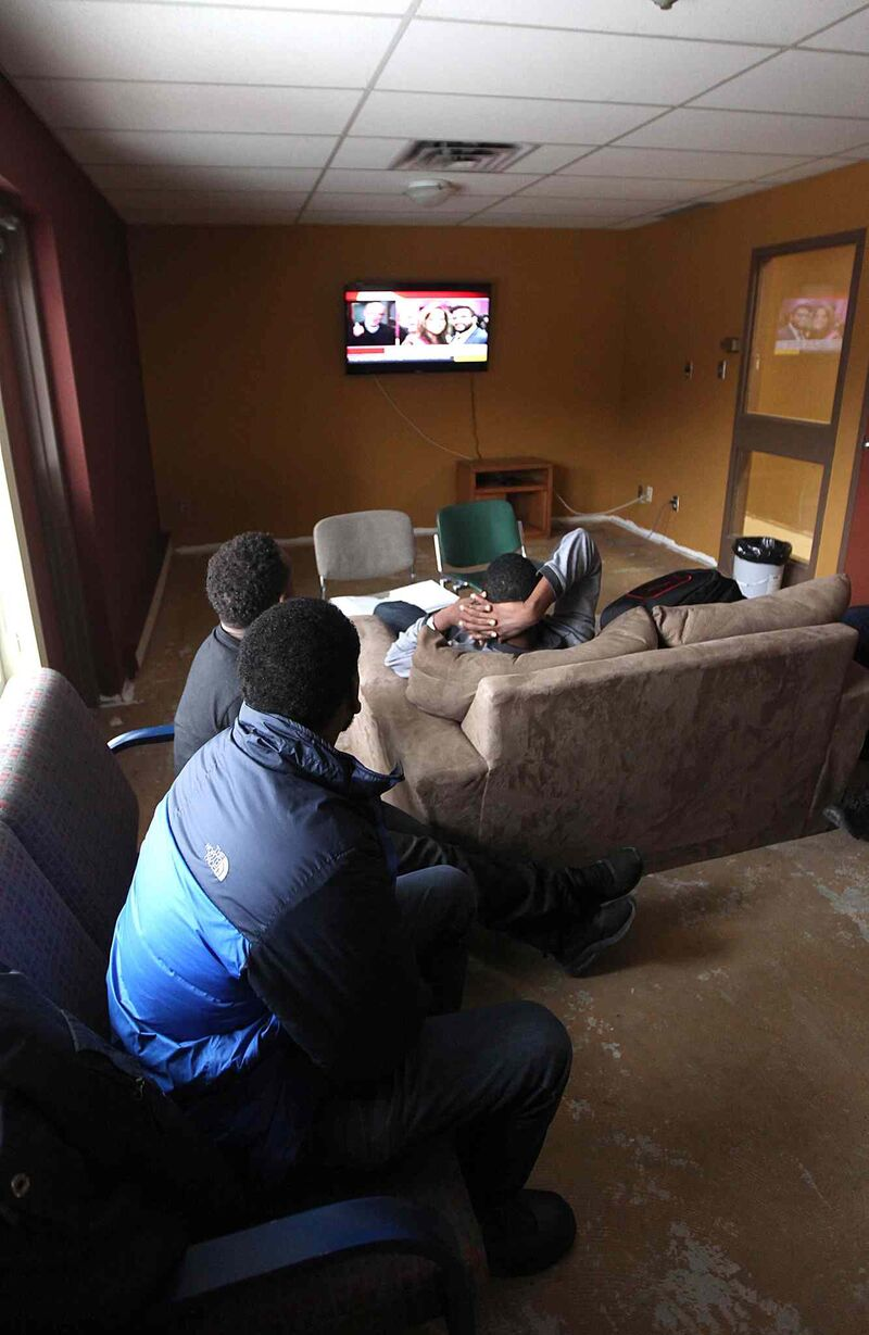 Asylum seekers watch the news in a  common room at the Salvation Army shelter.