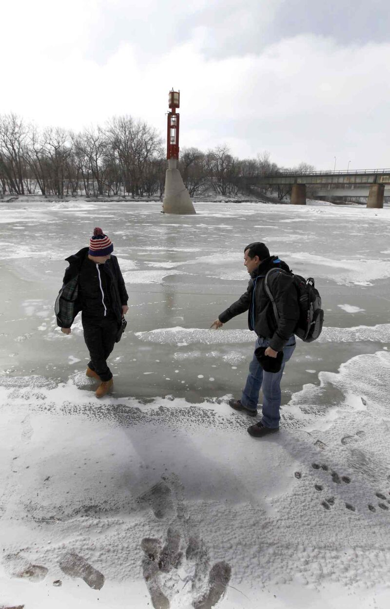 Shahadat Hossain (left) and Subir Barman take their first tentative steps on the frozen Assiniboine River Wednesday. Neither had ever seen a frozen waterway.