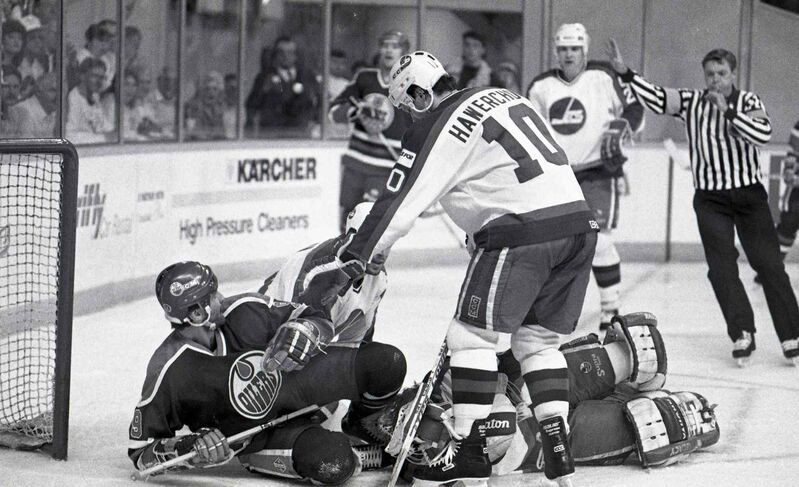 Dale Hawerchuk and Glenn Anderson (on ice) get tangled up. The two were later inducted into the Hockey Hall of Fame.