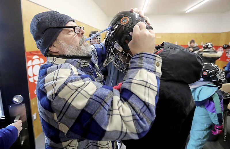 """Here's a moment from last February where [Turner] stopped working to make sure newcomers had their hockey helmets done up properly,"" photographer Trevor Hagan wrote on Twitter Wednesday. (Trevor Hagan / Winnipeg Free Press files)"