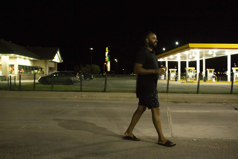 A truck driver walks back to his vehicle with a coffee.