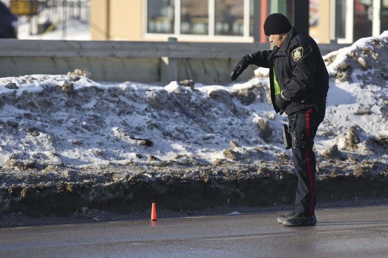 A Winnipeg police officer appears to be counting shell casings at the scene of a shooting Tuesday on Ellice Avenue between Strathcona and Empress streets. MIKE DEAL / WINNIPEG FREE PRESS </p>