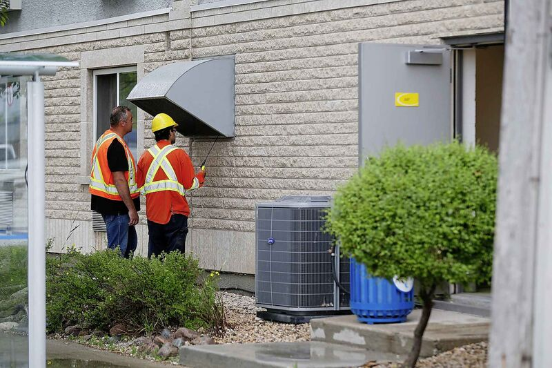 Gas workers check air quality at ventilation vents.