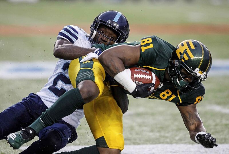 Toronto Argonauts Cassius Vaughn (26) tackles Edmonton Eskimos D'Haquille Williams (81) in Edmonton on Friday July 13, 2018.  (Jason Franson / The Canadian Press)