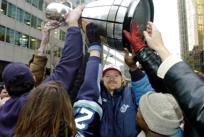 Toronto Argonaut Mike O'Shea (centre) takes the Grey Cup to the fans on the street during a parade celebrating the win in Toronto in 2004. (Aaron Harris / The Canadian Press files)