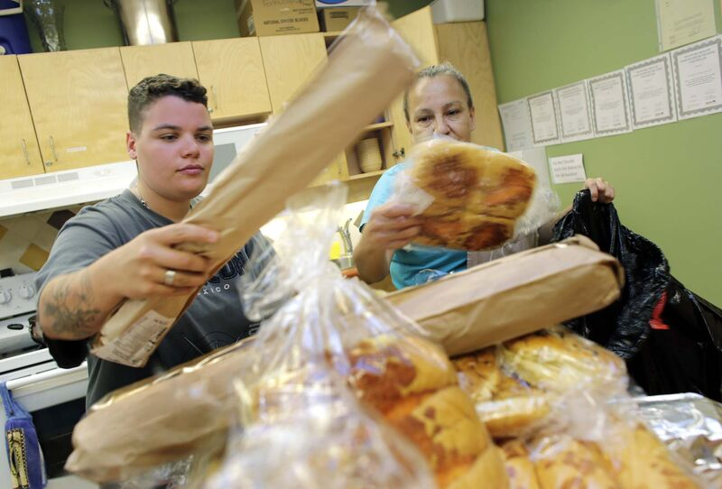 Shaina Zabinski (from left) and Loretta Stevenson inspect the food delivery.