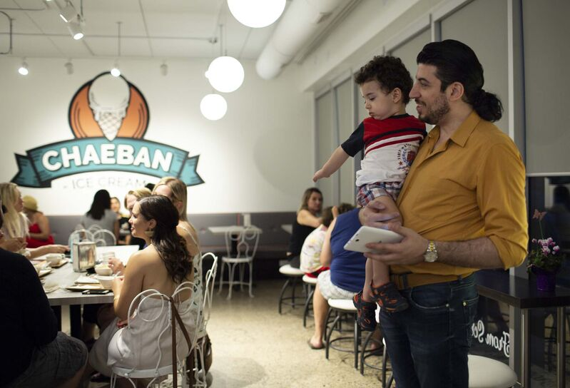 Tarek Turjman, and his son Muhammed, 3, wait to speak to their friend, the owner of Chaeban.