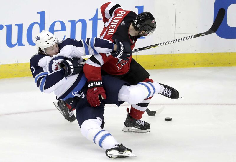 Winnipeg Jets defenseman Ben Chiarot, left, and New Jersey Devils right wing Kyle Palmieri collide while competing for the puck during the third period of an NHL hockey game.(Julio Cortez / The Associated Press files)
