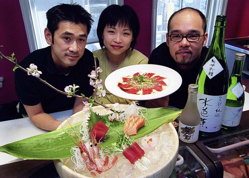 Cho Venevongsa (from left), his wife Tracey Chen and William Wong show off new style sashimi dishes at Wasabi on Broadway in 2000. (Joe Bryksa / Winnipeg Free Press files)