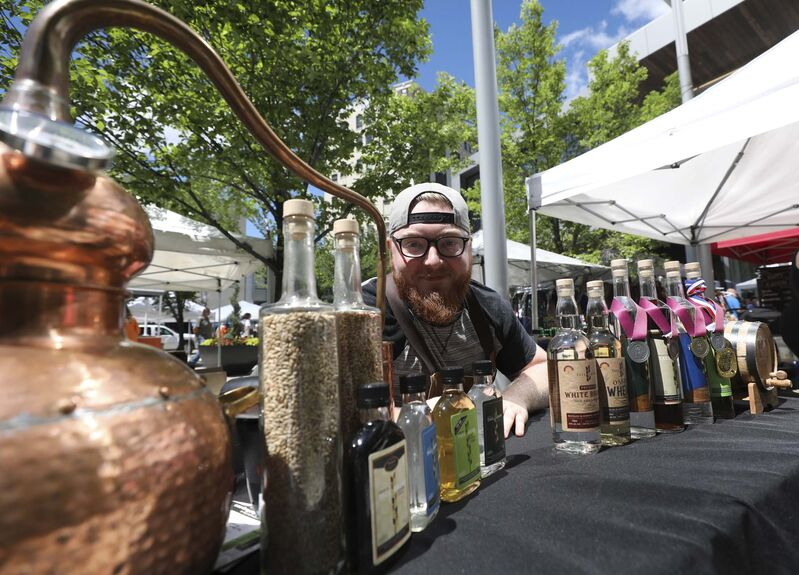 RUTH BONNEVILLE / WINNIPEG FREE PRESS</p><p>Jesse Hildebrand, Assistant General Manager with Capital K Distillery, peddles his wares at the downtown farmers' market at Hydro Place.</p>