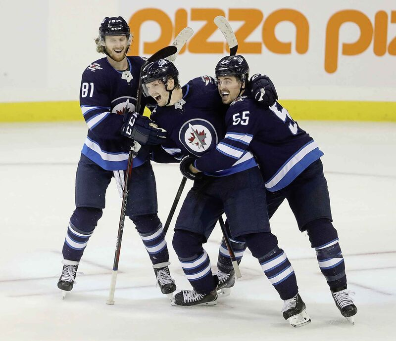 Winnipeg Jets' Kyle Connor (81), Jacob Trouba (8), and Mark Scheifele (55) celebrate after Trouba scored the game winning goal against the St. Louis Blues during overtime NHL hockey action in Winnipeg, Monday.