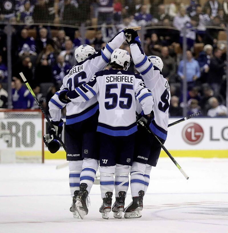 Winnipeg Jets' Blake Wheeler, Mark Scheifele and Andrew Copp celebrate after Wheeler scored the shootout winning goal against the Toronto Maple Leafs in Toronto, Wednesday.