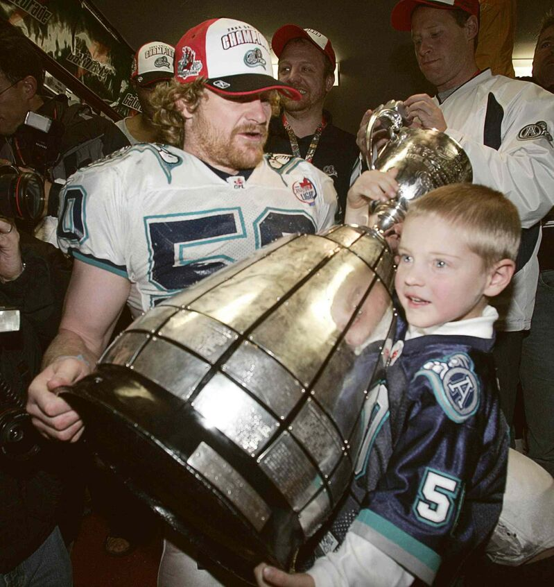 Toronto Argonauts' Michael O'Shea and his son Micheal, then 4, lift the CFL Grey Cup Sunday, Nov. 21, 2004 in Ottawa.  The Argonauts beat the B.C. Lions 27-19. (Tom Hanson / The Canadian Press files)