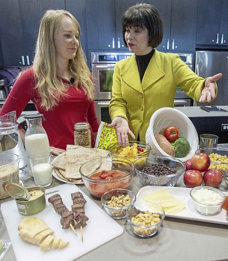 Health Minister Ginette Petitpas Taylor (right) and nutritionist Jessica Cole display samples of some of the food groups in the new Canada's Food Guide. (Ryan Remiorz / The Canadian Press)