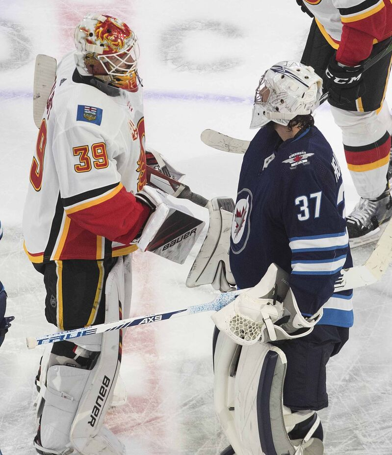Calgary Flames goalie Cam Talbot and goalie Connor Hellebuyck shake hands after the Jets were eliminated Thursday night.