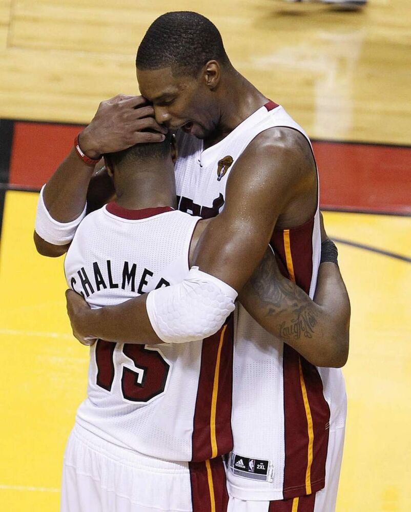 Miami Heat point guard Mario Chalmers (15) and power forward Chris Bosh embrace after winning Game 4 of the NBA finals basketball series against the Oklahoma City Thunder, Tuesday, in Miami. (AP Photo/Wilfredo Lee)