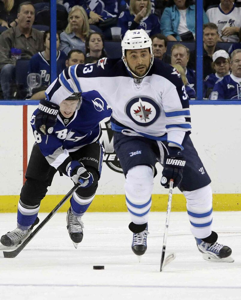 Winnipeg Jets defenceman Dustin Byfuglien (front) breaks out after getting past Tampa Bay Lightning winger Ondrej Palat during the first period.