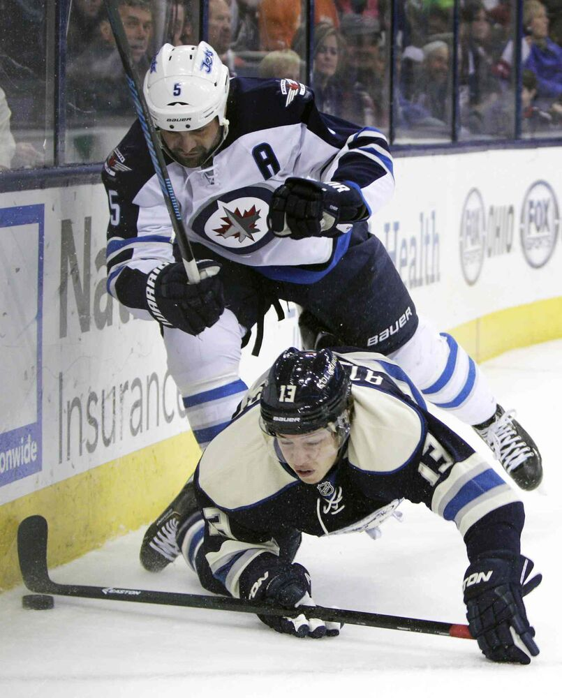 Jets defenceman Mark Stuart knocks down Blue Jackets Cam Atkinson Monday night. (Jay LaPrete / The Associated Press)