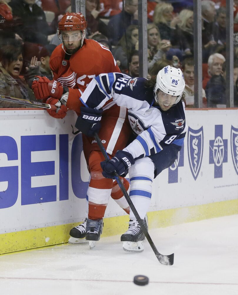 Jets centre Mathieu Perreault  out-muscles Red Wings defenceman Kyle Quincey in pursuit of the puck. (Carlos Osorio / The Associated Press)