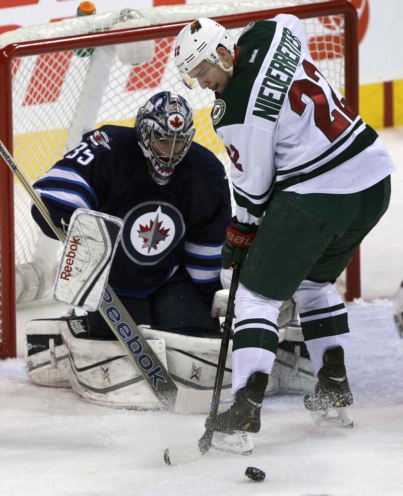 Winnipeg Jets goaltender Al Montoya is challenged by Minnesota Wild Nino Niederreiter during the first period. Montoya relieved Jets goalie Ondrej Pavelec after the Minnesota Wild scored three goals early in the period.