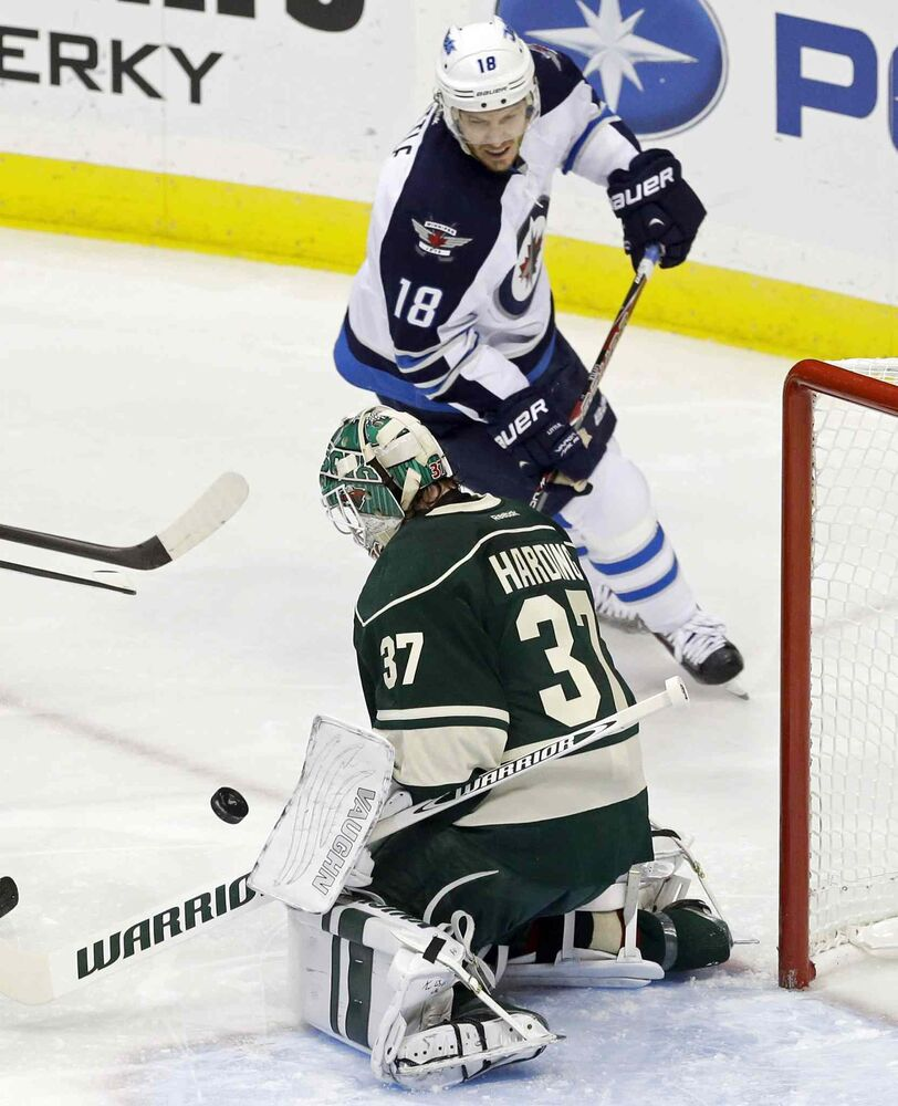 Bryan Little of the Winnipeg Jets races in for the rebound as Minnesota Wild goalie Josh Harding stops a shot in the first period. (Jim Mone / The Associated Press)