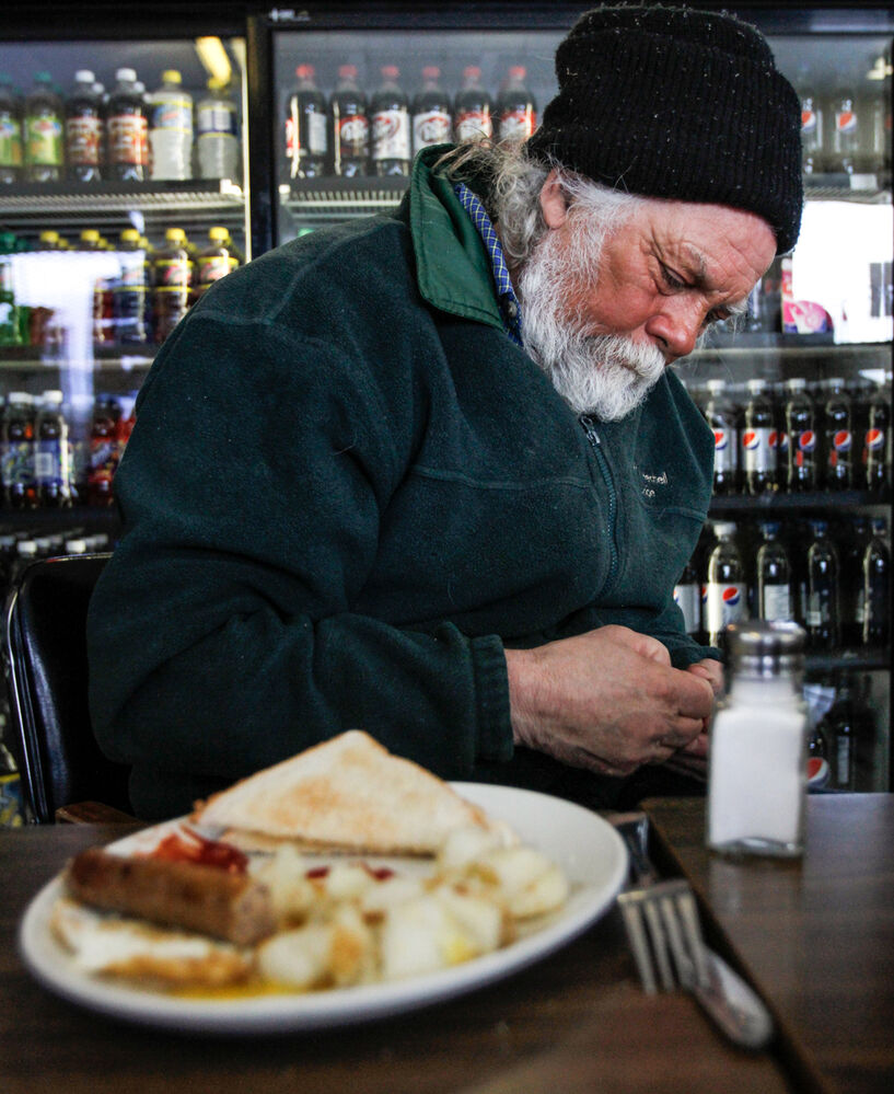 Prior to heading out on the ice, Kenyon reflects over breakfast at the Fairford Bridge Convenience store and restaurant in Fairford, MB. . (Jessica Burtnick / Winnipeg Free Press)