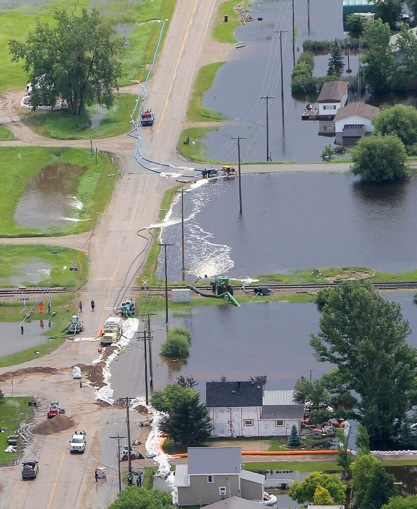 Crews work on floodwaters besieging Reston on Monday afternoon after a weekend of relentless rain and wind hammered southwestern Manitoba.  (Colin Corneau / Brandon Sun)