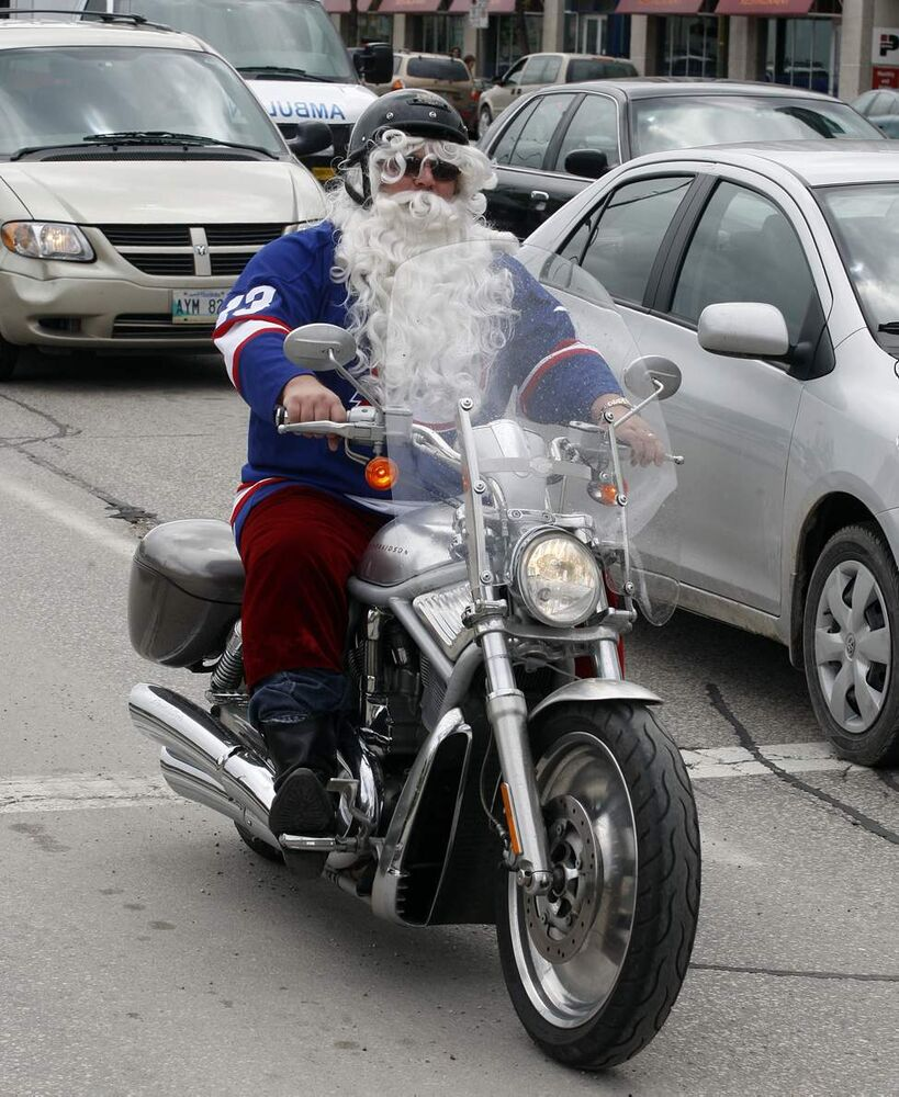 NHL comes back to Winnipeg - Yes, that's Santa riding on a Harley wearing a Selanne Jets jersey down Main Street after the rally at the Forks. (KEN GIGLIOTTI / WINNIPEG FREE PRESS)