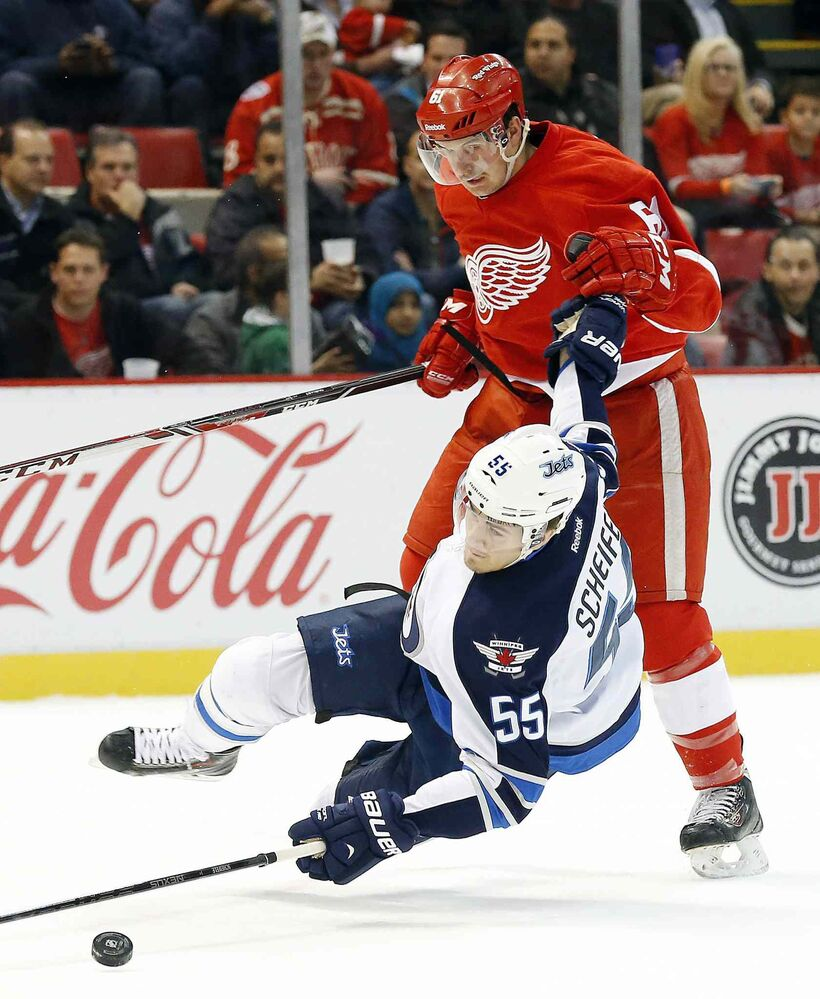 Winnipeg Jets centre Mark Scheifele is dumped by Detroit Red Wings defenceman Xavier Quellet in the first period.