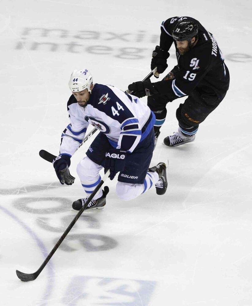 Winnipeg Jets' Zach Bogosian (44) is chased by San Jose Sharks' Joe Thornton (19) during the first period of Thursday's game in San Jose. (Marcio Jose Sanchez / The Associated Press)