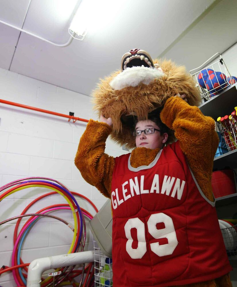 Noah puts on the costume for the school lion mascot, stored in the gymnasium's equipment room at Glenlawn Collegiate.  His role as the class clown at Windsor School seems to fit him well at his new school.   (RUTH BONNEVILLE / WINNIPEG FREE PRESS)