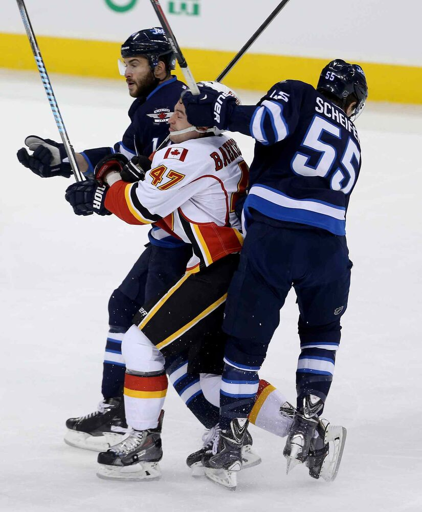 Winnipeg Jets' Anthony Peluso (14) and Mark Scheifele (55) sandwich Calgary Flames' Sven Baertschi (47) during first period NHL hockey action in Winnipeg Monday, November 18, 2013.