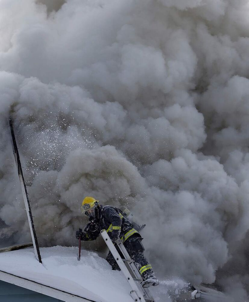 Winnipeg fire fighters had to make a hasty exit off the front porch roof as smoke came pouring out a second floor window at 868 Pritchard Ave. The occupant had left the house to go to the store when it caught fire. February 19, 2014  (KEN GIGLIOTTI / WINNIPEG FREE PRESS)
