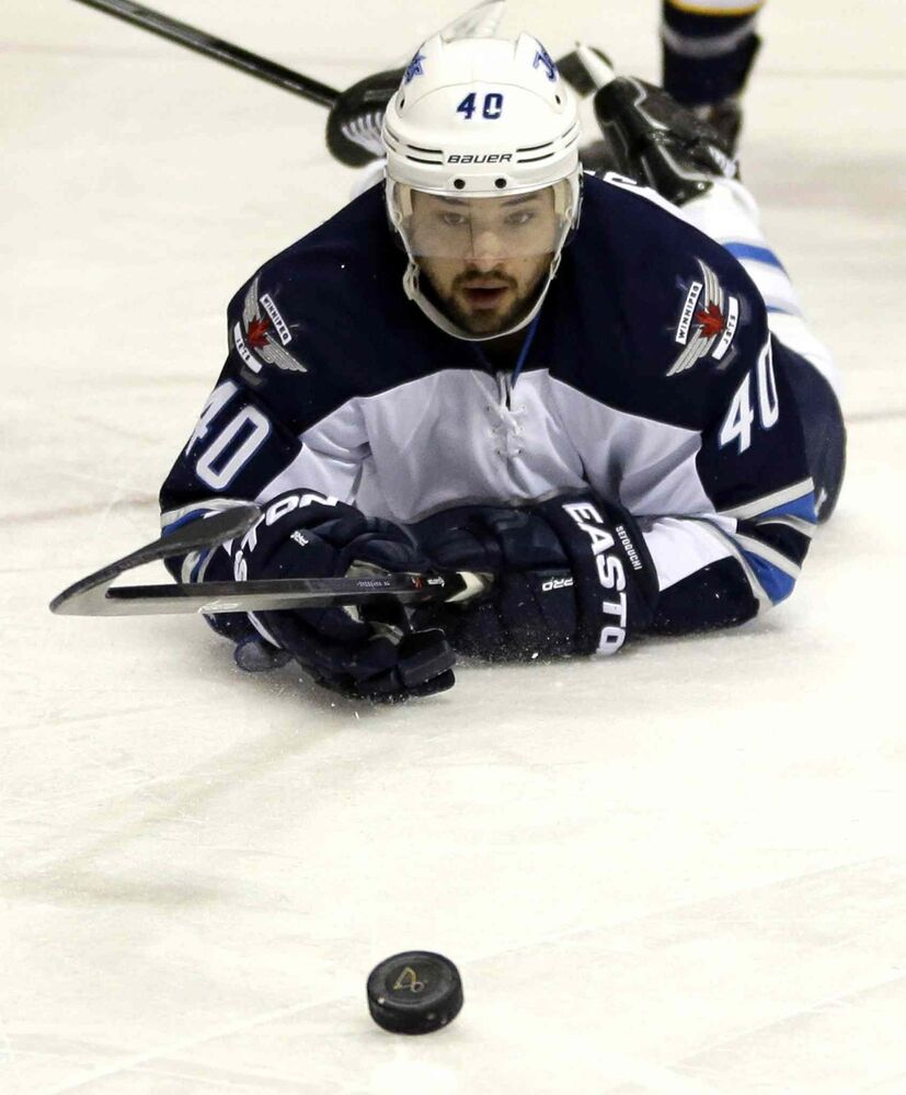 Winnipeg Jets' Devin Setoguchi keeps his eye on the puck after falling to the ice during the first period of Saturday's game. (Jeff Roberson / The Associated Press)