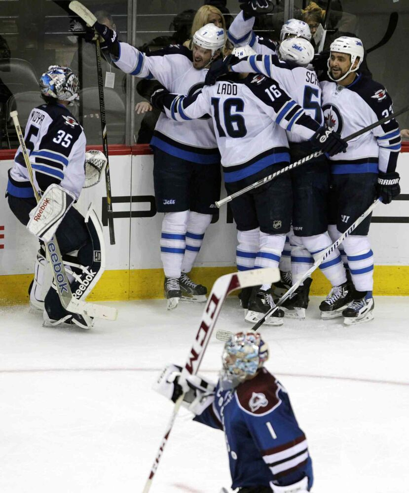 Winnipeg Jets goalie Al Montoya (left) skates toward his teammates to celebrate the team's overtime victory as Avalanche goalie Semyon Varlamov (bottom) skates to the bench. (Joe Mahoney / The Associated Press)