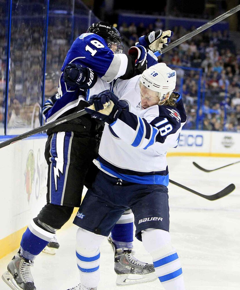 The sticks come up as the Tampa Bay Lightning's Ondrej Palat (left) collides with the Winnipeg Jets forward Bryan Little during the first period. (Dirk Shadd / Tampa Bay Times / MCT)
