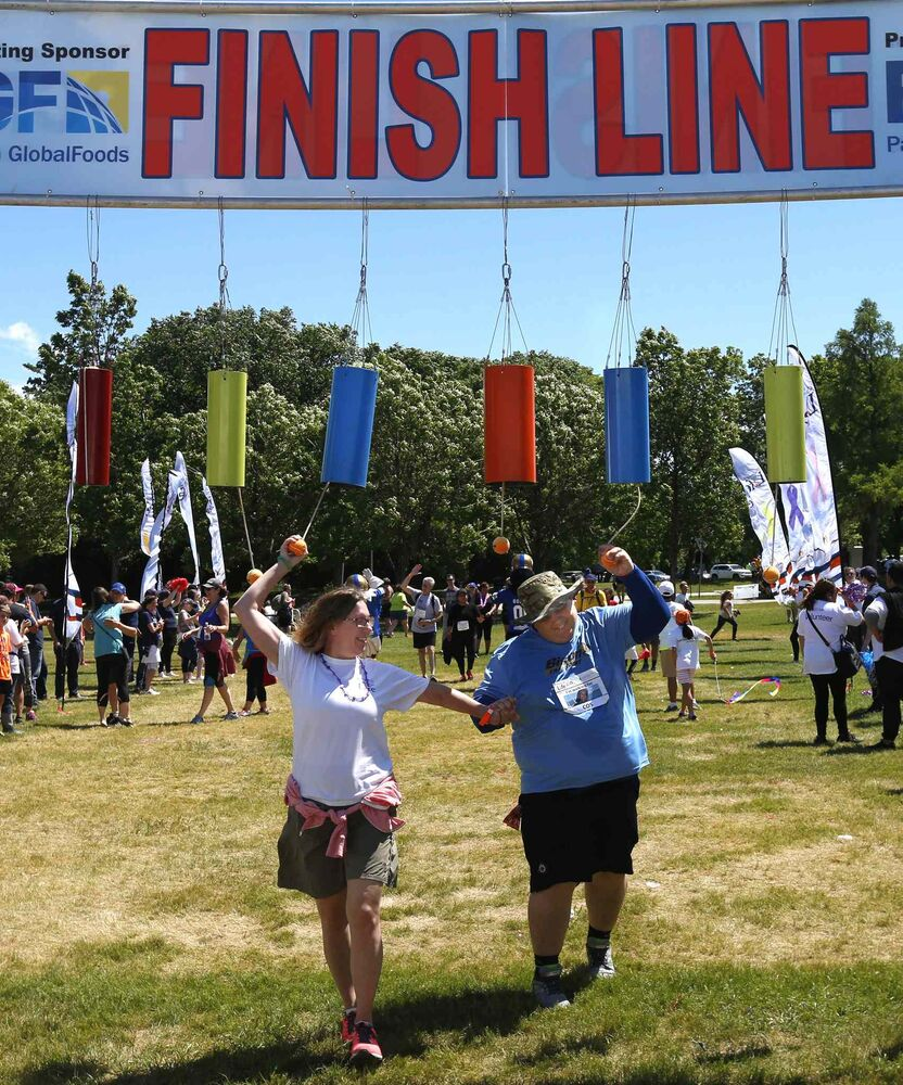 Friends and co-workers Paula Napier and Paul Arsenault ring the bell as they cross the finish line.<br>