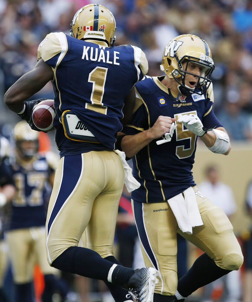 Winnipeg Blue Bombers' Ejiro Kuale and quarterback Drew Willy celebrate Kuale's fumble recovery against the Toronto Argonauts during the first half in Winnipeg Thursday.  (John Woods / THE CANADIAN PRESS)