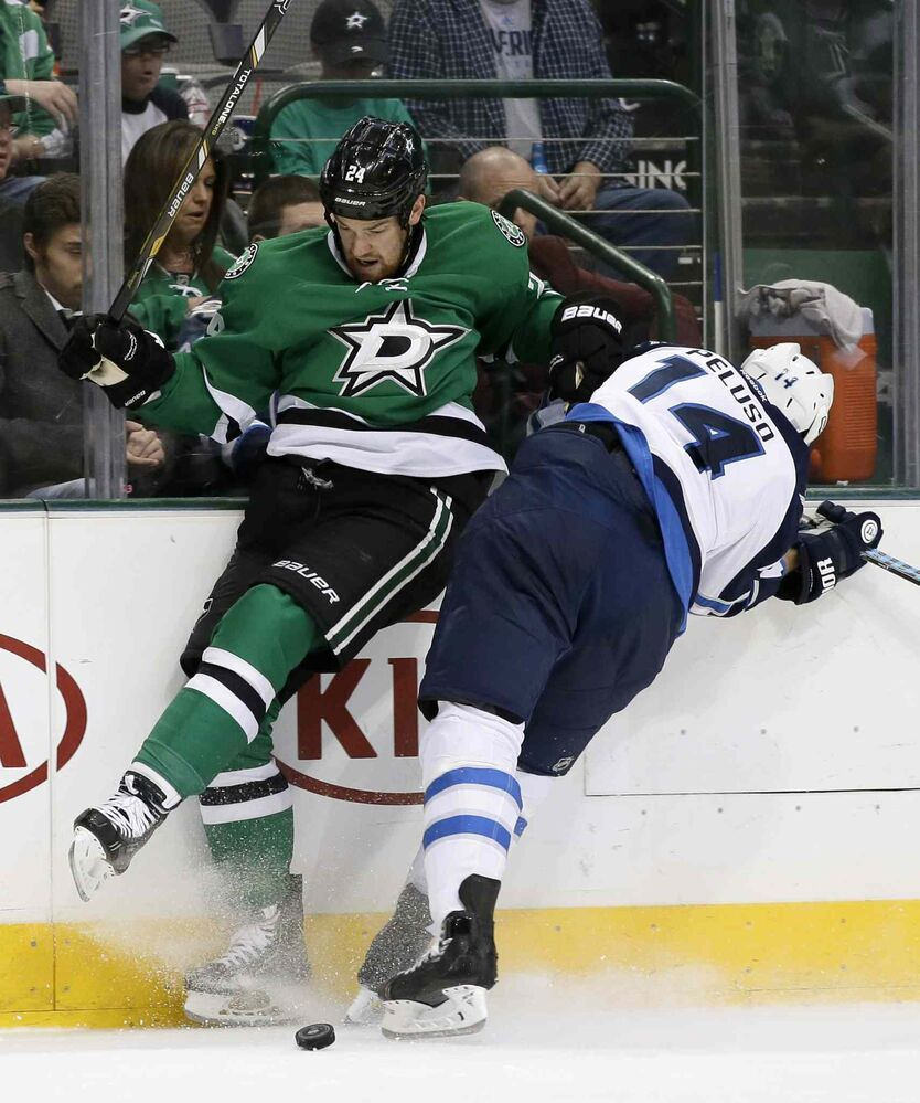 Dallas Stars defenceman Jordie Benn (left) and Winnipeg Jets winger Anthony Peluso collide as they race for a loose puck in the second period. (Tony Gutierrez / The Associated Press)