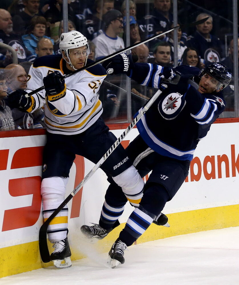 Winnipeg Jets' Blake Wheeler, right, hits Buffalo Sabres' Alexander Sulzer (#52) into the boards behind the Buffalo goal in the second period. (Trevor Hagan / The Canadian Press)
