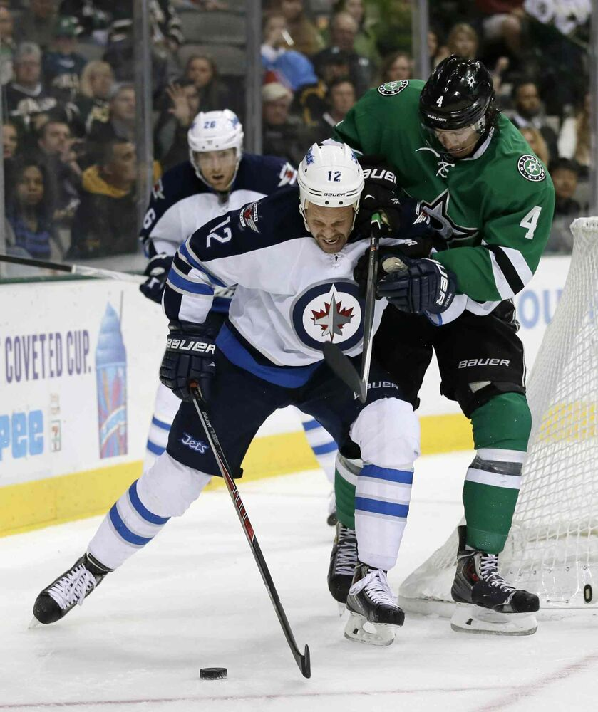 Winnipeg Jets center Olli Jokinen (centre) struggles against Dallas Stars defenceman Brenden Dillon in the second period.