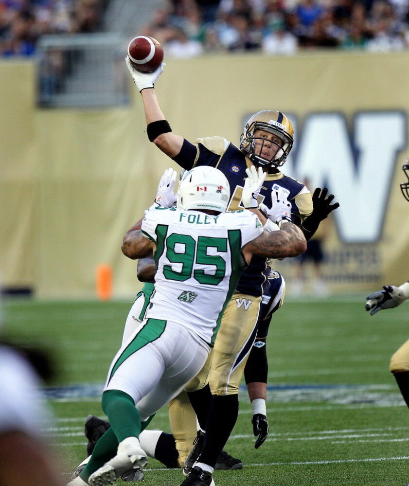 Winnipeg Blue Bombers Drew Willy goes up and over Saskatchewan Roughriders Ricky Foley (95) Thursday night at Inverstors Group Field in Winnipeg.