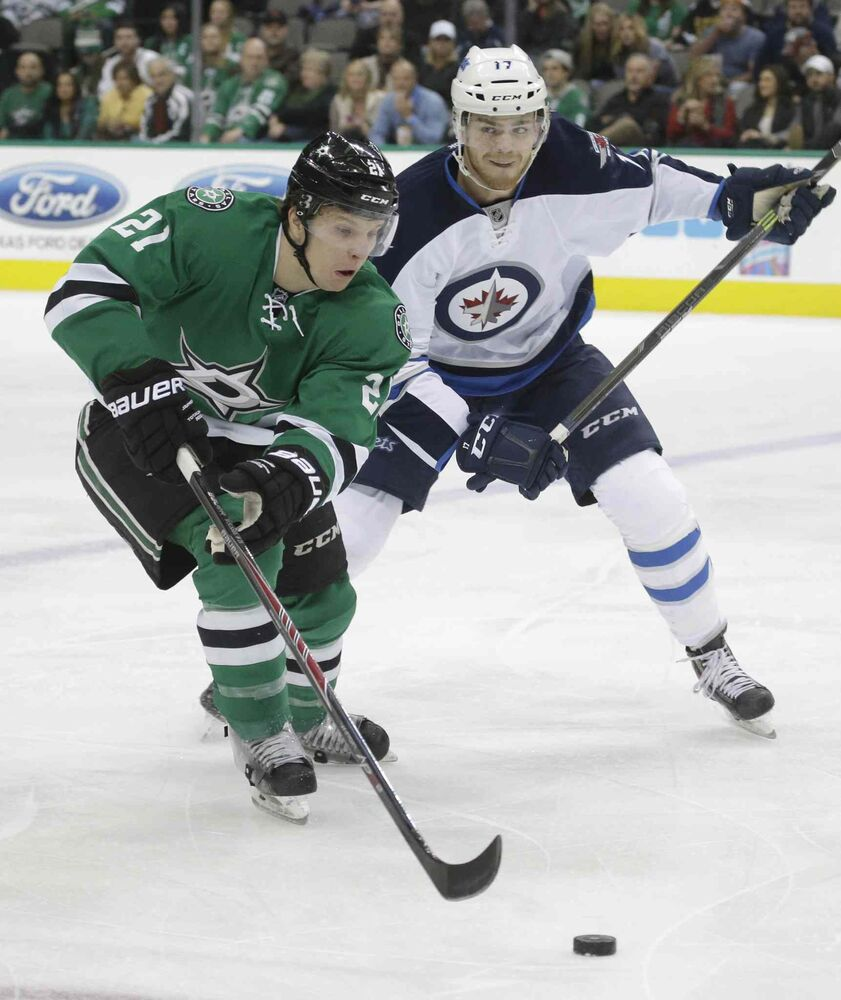 Dallas Stars left wing Antoine Roussel (21) skates with the puck against Winnipeg Jets left wing Adam Lowry (17) during the first period of Thursday's game. (LM Otero / The Associated Press)
