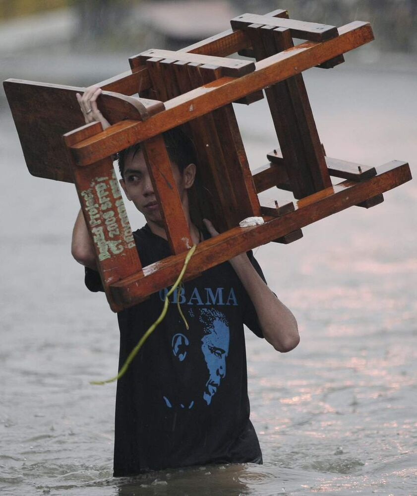 A resident wearing a shirt with a picture of US President Barack Obama carries a chair as he wades along a flooded area in Quezon City, north of Manila, Philippines, on Tuesday Aug. 7, 2012. Relentless rains submerged half of the sprawling Philippine capital, triggered a landslide that killed eight people and sent emergency crews scrambling Tuesday to rescue and evacuate tens of thousands of residents.  AP Photo / Aaron Favila