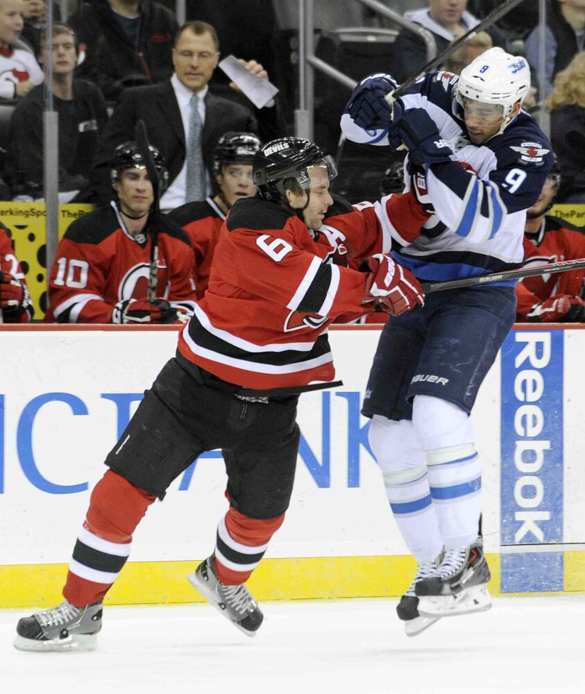 New Jersey Devils defenceman Andy Greene checks Winnipeg Jets forward Evander Kane during the first period.