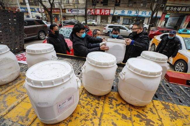 Workers unload canisters of disinfectant from a truck in Wuhan in central China's Hubei Province, Tuesday, Jan. 28, 2020. Hong Kong's leader announced Tuesday that all rail links to mainland China will be cut starting Friday as fears grow about the spread of a new virus. (Chinatopix via AP)