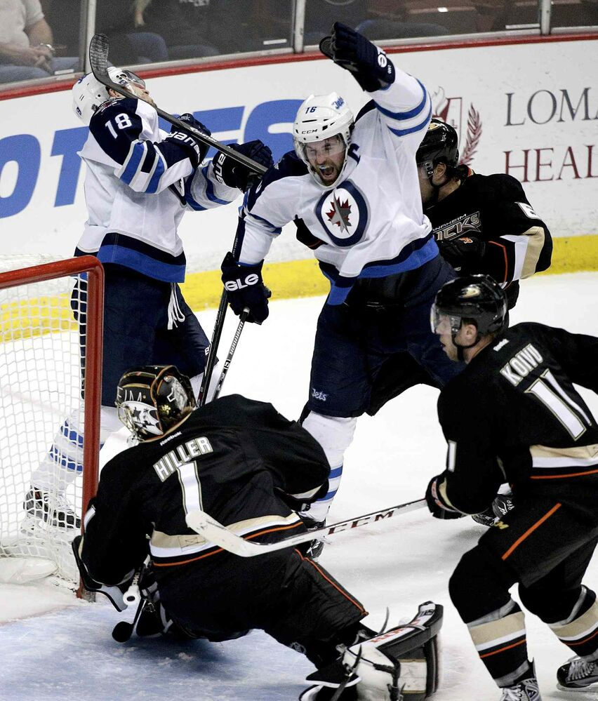 Winnipeg Jets' Andrew Ladd, top right, celebrates a first-period goal by teammate Bryan Little (18) in front of Anaheim Ducks' goalie Jonas Hiller and Saku Koivu during Tuesday's game in Anaheim.